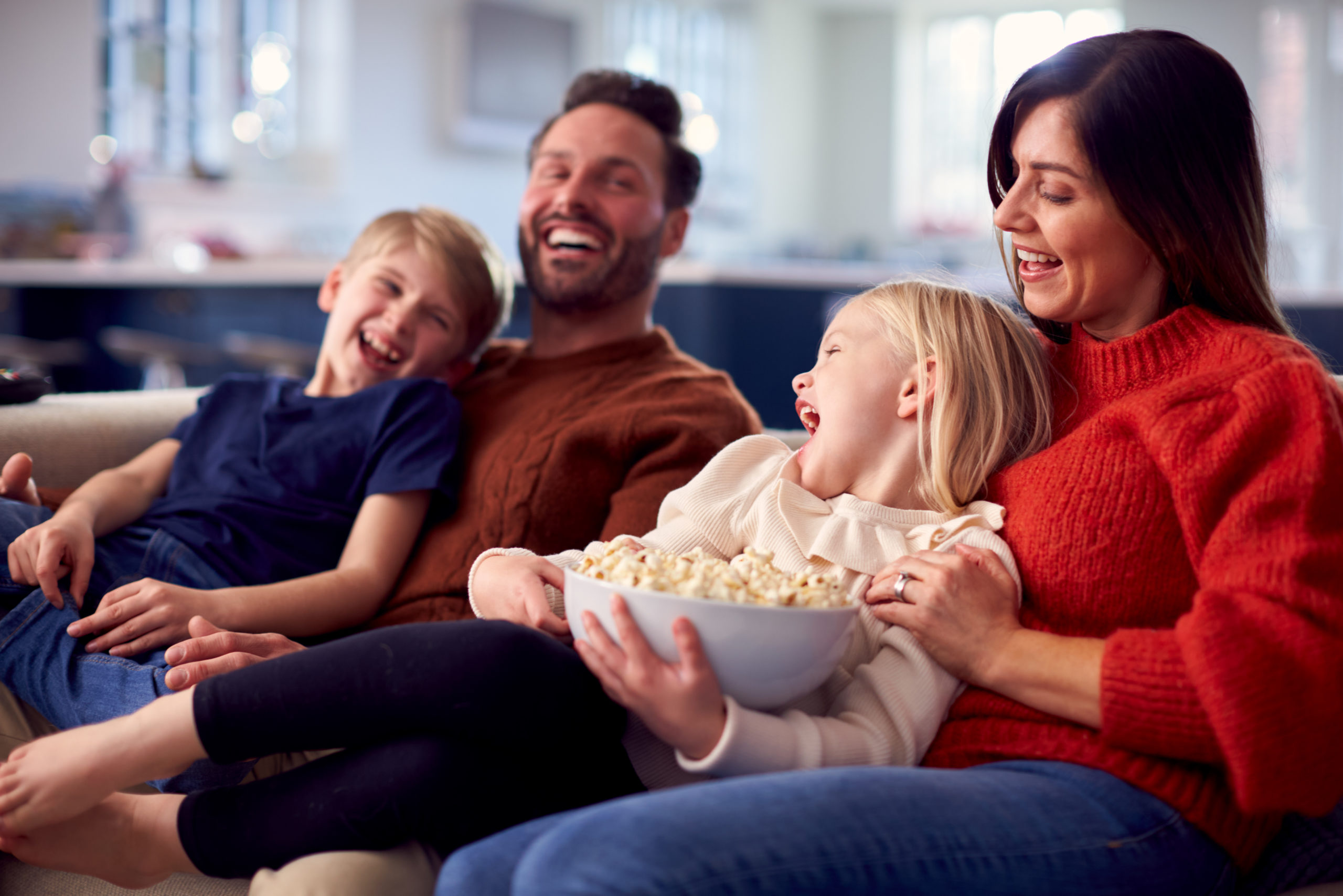 Family Sitting On Sofa With Popcorn Laughing Watching Comedy On TV Together
